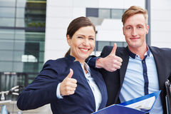 Two happy consultants holding their. Two happy consultants with files holding their thumbs up Royalty Free Stock Images