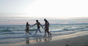 Two Happy Couple Walking On Beach Holding Hands At Sunset, Young People Tourists Communication On Summer Sea Vacation. Slow Motion 60 stock video footage