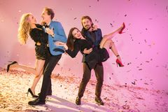 Couples dancing on party. Two happy couples dancing on party with confetti on pink stock images
