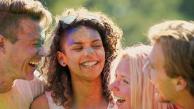Two happy couples enjoying double date at colours festival on bright sunny day. Stock footage stock footage