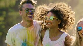 Two happy couples having good time together, hugging and jumping at festival. Stock footage stock footage