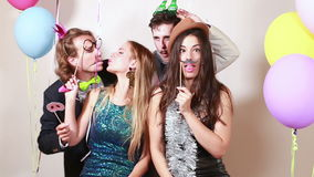 Two happy couples having a great time in photo booth. Two happy couples having great time in party photo booth stock footage