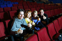 Two happy couples look at camera and thumb up in cinema theater. Royalty Free Stock Image