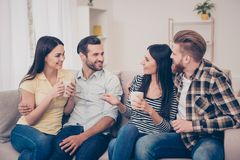 Two happy couples sitting on cozy sofa at home, having nice conversation and embracing. A weekend with best friends, what can be stock photos