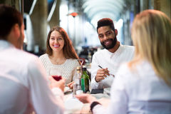 Two happy couples sitting at outdoor restaurant royalty free stock photography