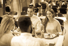 Two happy couples sitting at outdoor restaurant royalty free stock photos