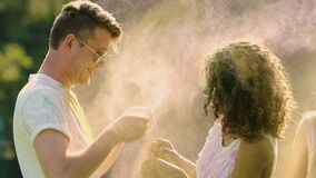 Two happy couples throwing powder paint at each other, flirting and laughing. Stock footage stock video