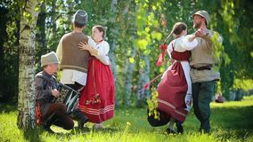Two happy couples in traditional Russian clothes dancing on the field by the accordion music. Mid shot stock footage