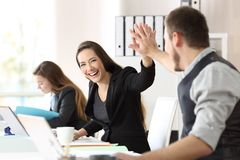 Two happy coworkers celebrating success at office. Two happy coworkers celebrating success giving five at office royalty free stock photos