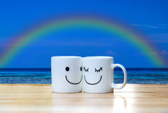 Two happy cups on wood table under blue sea, sky and rainbow. Two happy feelings cups on wood table under blue sea, sky and rainbow Stock Image
