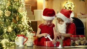 Two happy cute children in Santa hat with present have a Christmas. New year Christmas concept. Happy children holding a. Red gift box with both hands stock video