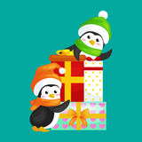 Two happy cute Christmas penguin in hat and scarf are a stack of Christmas gifts on the eve of the new year. Greeting Stock Photography