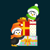 Two happy cute Christmas penguin in hat and scarf are a stack of Christmas gifts on the eve of the new year. Greeting Royalty Free Stock Image