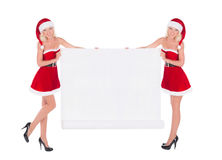 Two happy cute Santa women with christmas poster isolated on whi Royalty Free Stock Image