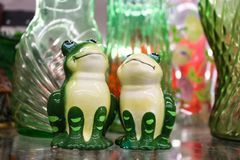 Two happy decorative frogs gaze upwards surrounded by green and pink glass. Two happy decorative green frogs gaze upwards surrounded by green and pink glass Stock Photography