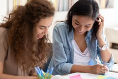 Two happy diverse girls college friends studying together in campus royalty free stock images