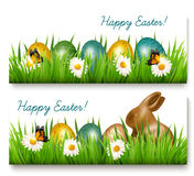 Two Happy Easter banners with Easter eggs and green grass Vector Stock Photos
