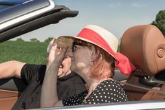 Happy older woman with a sun hat and her partner in a luxury convertible car. Two happy elderly people with a luxury convertible car on a sunny day stock photo