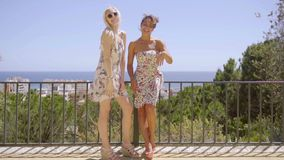 Two happy elegant young women standing waving. Two happy elegant young women standing on an outdoor patio waving and laughing at the camera in sunglasses and stock footage