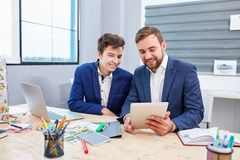 Two office workers look at the tablet and smile. stock photo