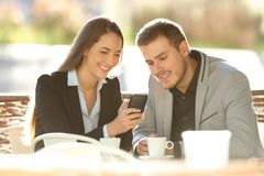 Two executives using a smart phone in a coffee shop. Two happy executives using a smart phone sitting in a restaurant terrace with a warm light in the background royalty free stock image