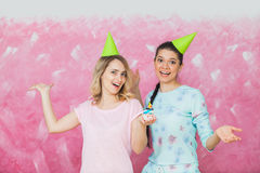 Two happy expressive girls celebrate birthday party with cupcake. And caps over pink background Royalty Free Stock Images
