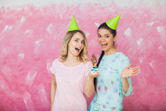 Two happy expressive girls celebrate birthday party with cupcake. And caps over pink background Royalty Free Stock Photos