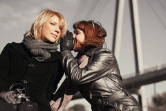 Two happy fashion women teeling secrets outdoor Stock Image