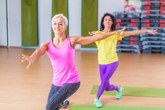 Two happy female fitness models dancing Zumba, doing aerobic exercises working out to lose weight in gym with colorful Stock Photo