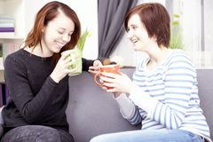Two happy female friends with coffee cups Stock Photos