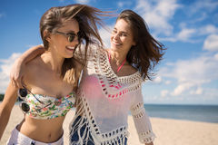 Two happy female friends embracing each other on beach Stock Photos