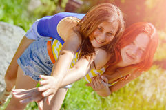 Two happy female friends hugging in green summer park Royalty Free Stock Photography