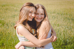 Two happy female friends hugging in green summer park Royalty Free Stock Photo
