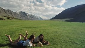 Two happy female friends lying on in the green grass against the background of the mountains. Trendy hipster girls relaxing on the grass. Portrait of a summer stock video footage