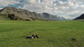 Two happy female friends lying on in the green grass against the background of the mountains. Trendy hipster girls relaxing on the grass. Portrait of a summer stock video