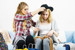Two happy female friends after shopping. Two happy joyful women having fun after shopping, picking outfit in closet. Female friends fooling around royalty free stock images