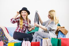 Two happy female friends after shopping. Two happy joyful women having fun after shopping, picking outfit in closet. Female friends fooling around royalty free stock photo