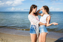 Two happy female friends standing together on beach hugging royalty free stock image