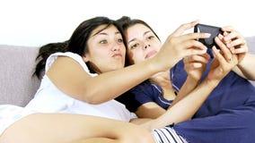 Two happy female model taking selfie having fun at home stock video