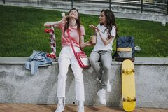 Two happy female skater having coffee break royalty free stock images