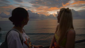 Two happy female travelers talking and laughing at the sunset against a background of the sea. Blonde and brunette are. Two happy female travelers are talking stock video footage