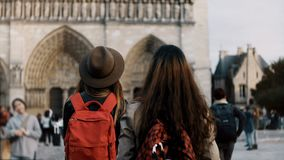 Two happy female walking with red backpacks near the Notre Dame, famous cathedral or church in Paris, France. Traveling girls exploring the beautiful sight stock video footage