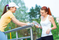 Two happy fitness women drinking water Stock Image