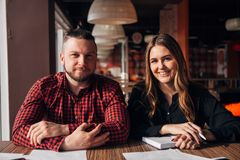 Two happy freelancer smiling at camera in cafe Stock Images