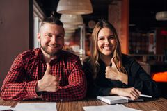 Two happy freelancers smile at the camera in cafe finger up, good job Royalty Free Stock Photos
