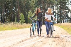Two happy friends with bicycles Stock Images
