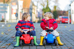 Two happy friends boys playing with big old toy car, outdoors Stock Image