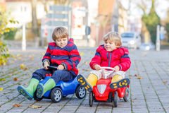 Two happy friends boys playing with colorful toy car, outdoors Stock Photo