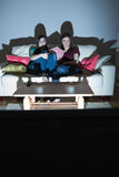Two happy friends on the couch watching tv together in the dark. At home in the living room Stock Photography