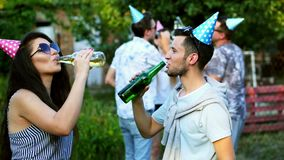 Two happy friends dancing and talking, man and woman drinking beer on summer party, people on the background, wearing stock footage